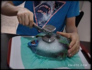 Iguana robot dentro de un huevo formado con hielo; NIH la intenta abrir con un martillo de cocina.